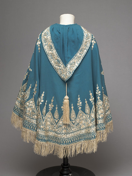 Child's cape.  Twilled peacock blue woollen cloth, embroidered in cream silk thread, with a cream tassel on the hood; Anglo-Indian, 1860-70, V&A