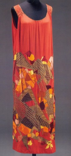 Evening dress of multi-coloured silk and velvet appliqué on red silk. Designed by Natalia Goncharova for Maison Myrbor, Paris, about 1923, V&A