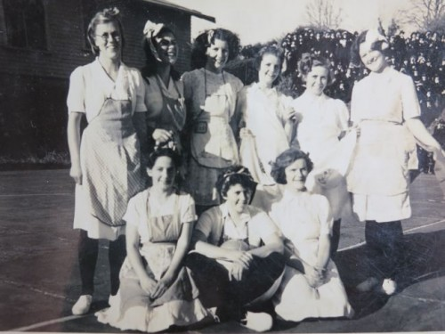 "Girls in aprons, 1940s.  ""Back Row from left: H. Smith, M Boyes, M Swaff, ord M. Howard, W Walsh, M Harris, A Ching, J Lucre, T Harley"