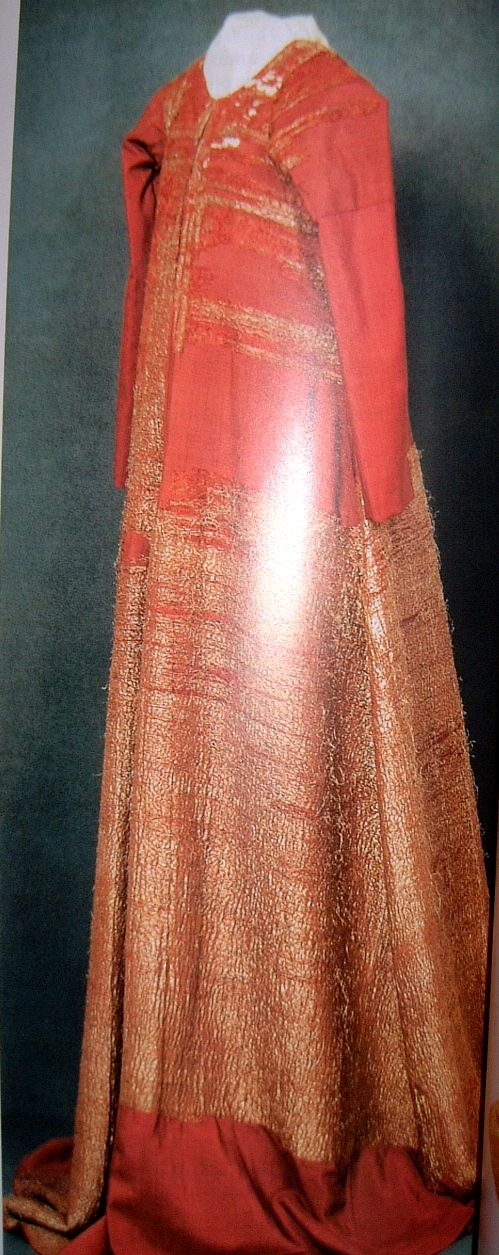 Gown of Italian gold brocade with a pomegranate design in gold on a reddish-violet silk ground.  First half of the 15th century.