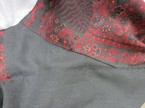 The underarm seam and bottom of the bodice drape