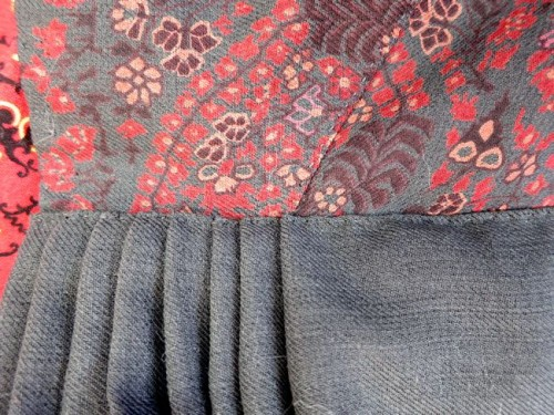 Running backstitches on the bodice of the 1813 Kashmiri dress, backstitches hold the skirt on