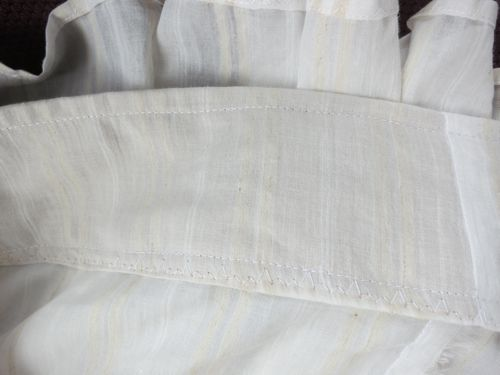 The stiff brown linen hem support seen through the sheer muslin