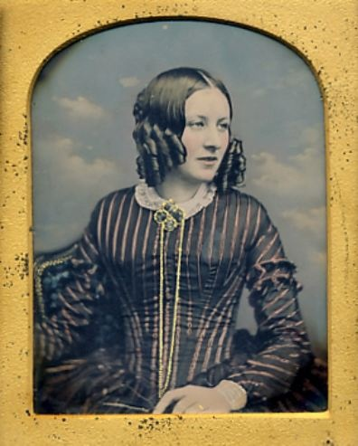 ca 1850's hand-tinted daguerreotype portrait of a young woman posed in front of a cloud backdrop