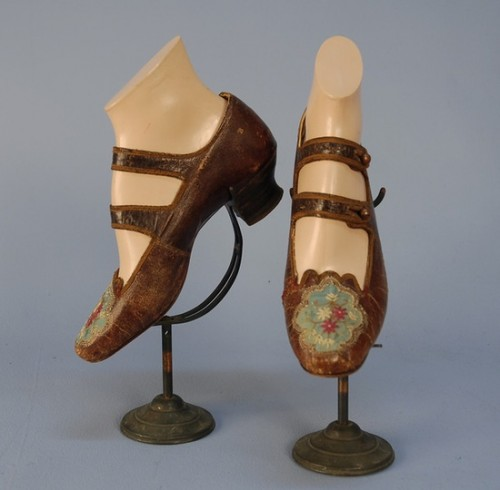 1870's shoes of brown leather with double button strap, stacked wooden heel, the toe having a cutout scalloped oval inset with floral embroidered blue silk faille