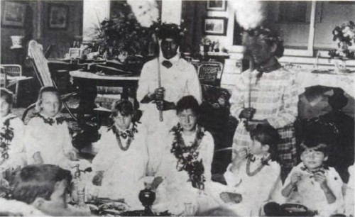 Young Kaiulani (between the two kahili bearers) enjoy luau with friends at Ainahau. 1880s