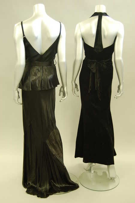 A bias-cut black ciré satin evening gown, early 1930s, adorned with two large floral rosettes with gold lamé centres embroidered roundels to skirt, and attached belt.  Augusta