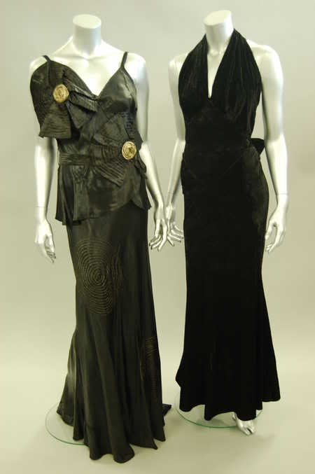 A bias-cut black ciré satin evening gown, early 1930s, adorned with two large floral rosettes with gold lamé centres embroidered roundels to skirt, and attached belt.  Augusta Auctions?