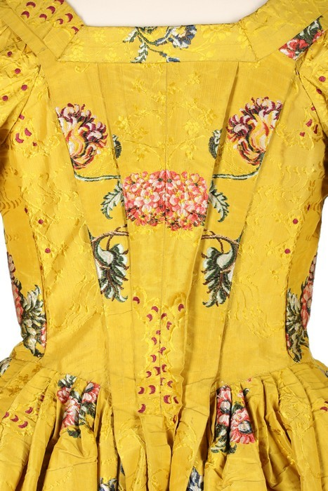 Robe à l'anglaise, England (Spitalfields), c. 1750. Yellow brocaded silk, woven with brightly coloured large-scale oriental poppies, posies and swags, the ground figured with arabesques and wine silk spotted cartouches, linen lining, trimmed with pinked furbelows; stomacher trimmed with rosettes and braid, sold by Kerry Taylor Auctions