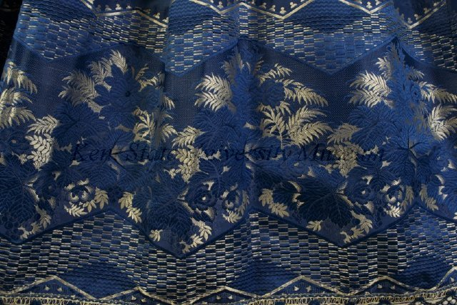 Blue silk taffeta evening dress with two-tier skirt. All hems are finished with a border of silver floral jacquard ribbon and fringe. American, ca. 1855 Silk taffeta, jacquard woven ribbon, silk fringe, KSUM 2005.6.4 a-d