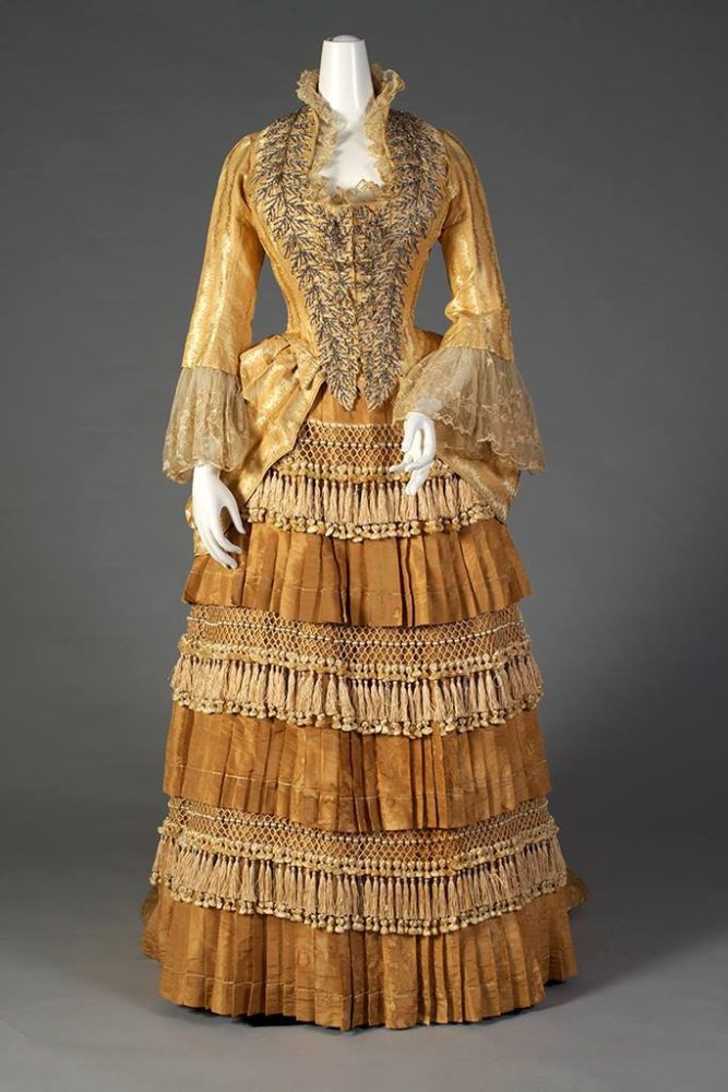 "Gold silk dress with tiered, tasseled skirt Label- ""Mrs. W. Wilds, Auburn, NY"" American, ca. 1879-80, SIlverman:Rodgers, Kent State University Museum 1983.1.156 ab"