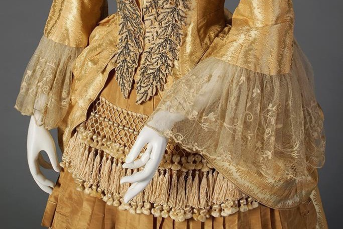 "Gold silk dress with tiered, tasseled skirt Label- ""Mrs. W. Wilds, Auburn, NY"" American, ca. 1879-80, Silverman:Rodgers, KSUM 1983.1.156 ab"