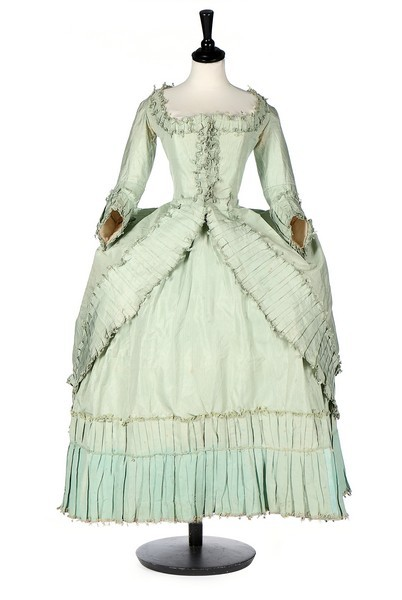 Robe, French, circa 1780, fastening with hooks and eyes, with with box pleated and fly-braid edged robings, fitted back skirts with fixed green silk cords, sold by Kerry Taylor Auctions