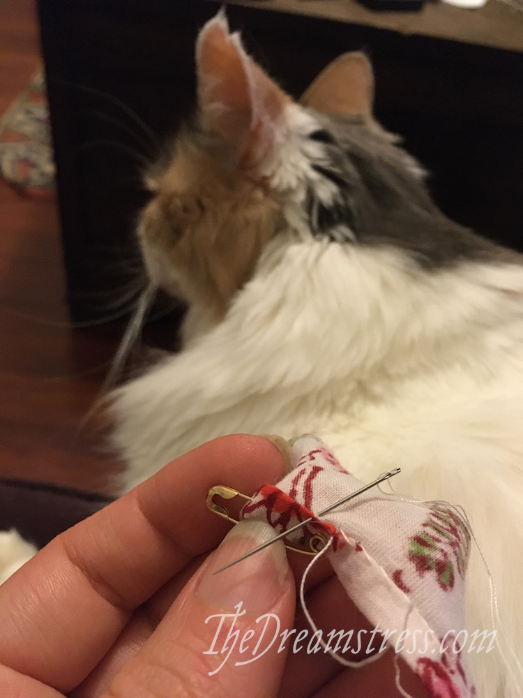 In the foreground, a hand sewing a narrow hem in floral chintz, In the background, a calico cat