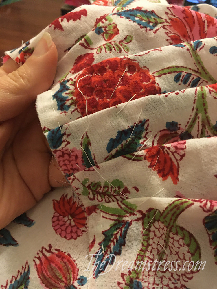 A hand holding a length of floral fabric with pleats secured with basting stitches