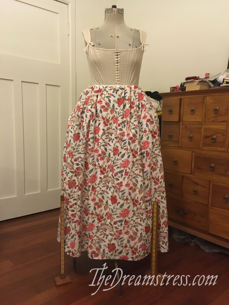 A dressform wearing stays and a brightly coloured floral petticoat