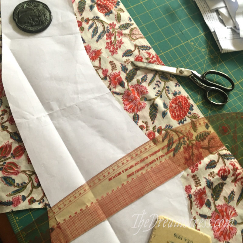 A sleeve pattern piece positioned on floral fabric