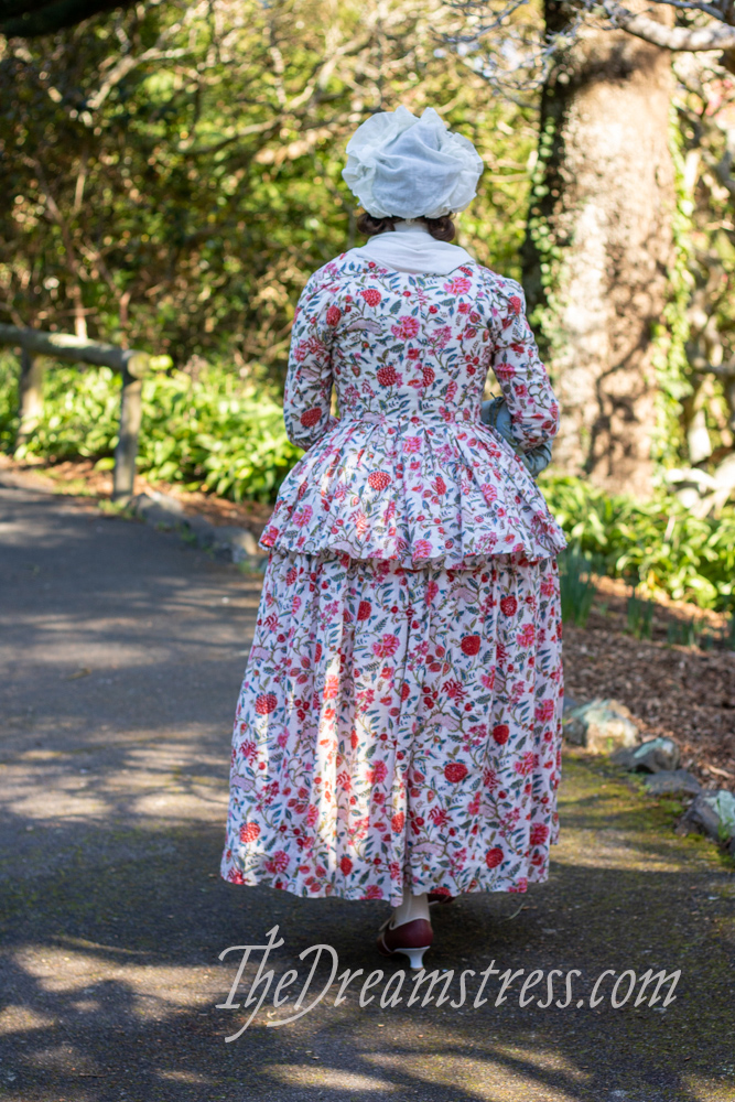 A woman in floral patterned 18th century garb walking away from the camera along a park path