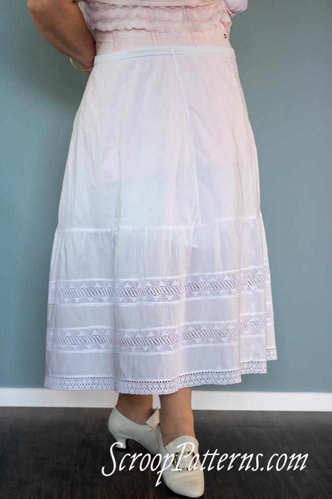 A woman wearing a white petticoat stands against a blue wall.
