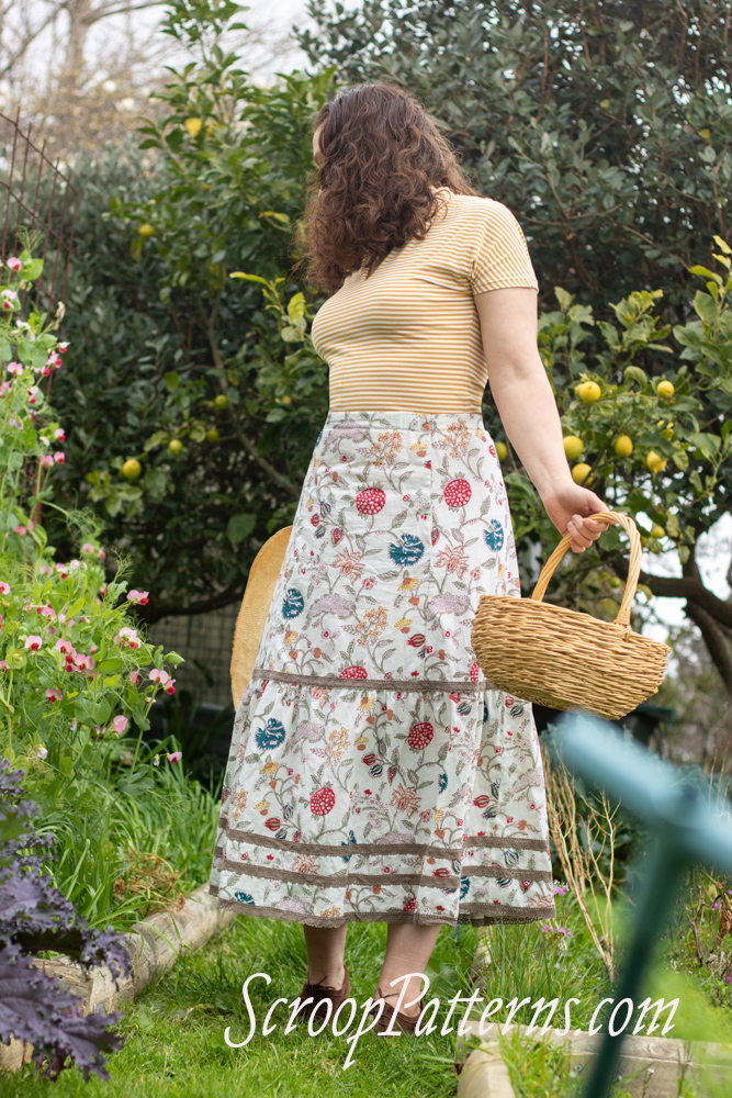 Image: a woman with curly hair wearing a yellow shirt and a floral skirt with lace.
