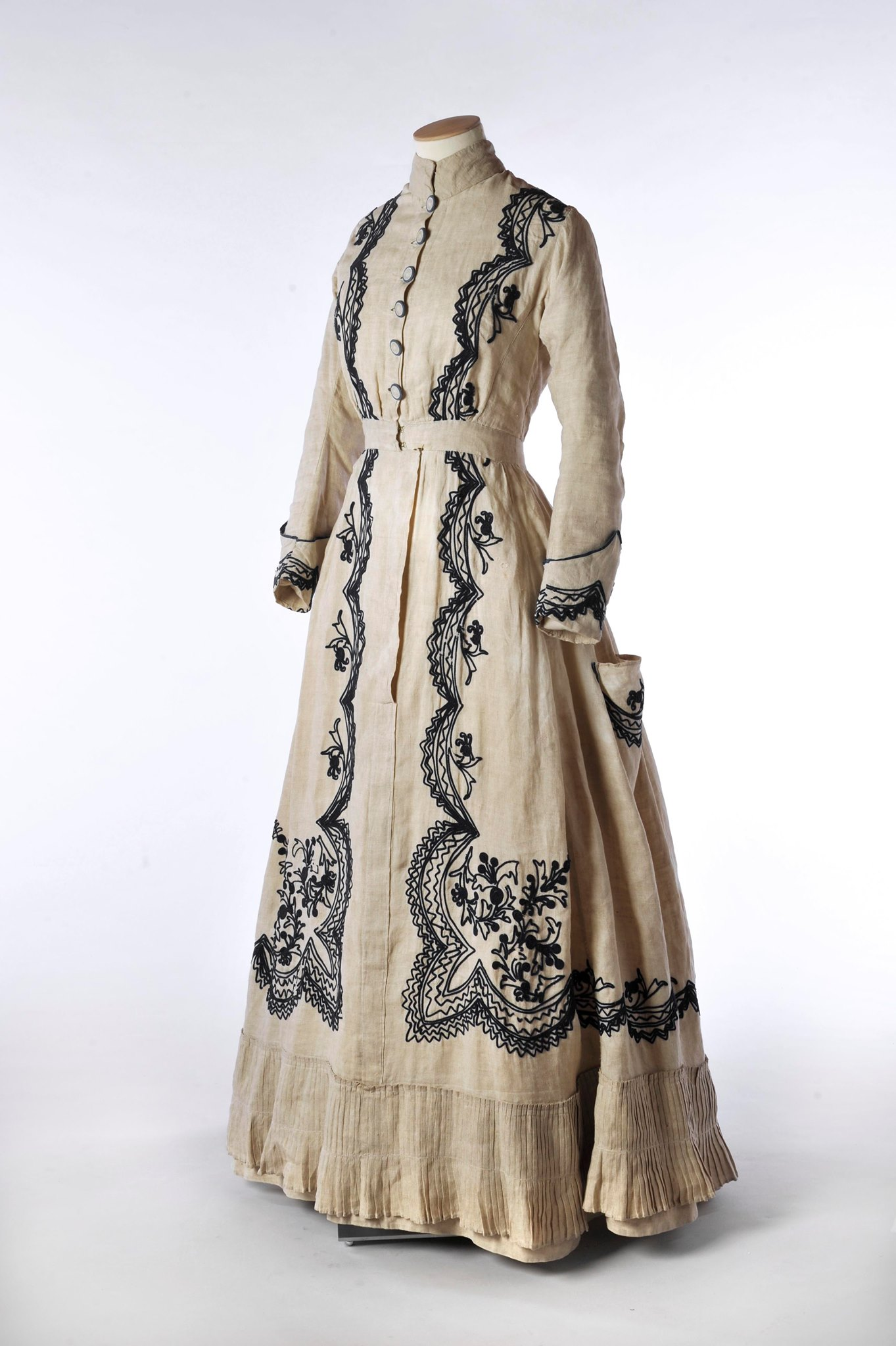 Image showing an ecru full length dress with buttons down the front and elaborate black embroidery
